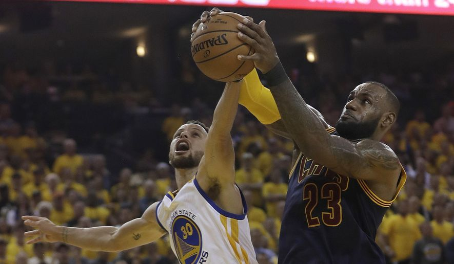 Cleveland Cavaliers forward LeBron James (23) grabs a rebound against Golden State Warriors guard Stephen Curry (30) during the first half of Game 1 of basketball's NBA Finals in Oakland, Calif., Thursday, June 1, 2017. (AP Photo/Marcio Jose Sanchez)