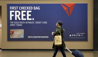 FILE - In this Tuesday, March 24, 2015, file photo, a traveler walks past a sign advertising a Delta credit card at Seattle-Tacoma International Airport in SeaTac, Wash. Checked-bag fees and restrictions on budget fares have increased the costs and hassles for airline travelers with luggage. But an airline credit card can eliminate the expense of checking a bag and some of the limits on no-frills fares. (AP Photo/Elaine Thompson, File)