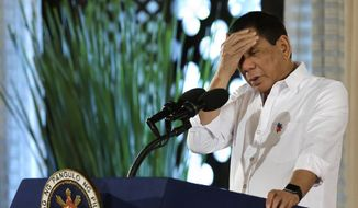Philippine President Rodrigo Duterte touches his head during his speech at the swearing in of officials of various municipalities at the Malacanang presidential palace in Manila, Philippines, on Thursday, June 1, 2017. Duterte declared martial law in the Mindanao region, the southern third of the Philippines, and poured in troops backed by airstrikes, artillery fire and tanks to crush the urban insurrection. (AP Photo/Aaron Favila)