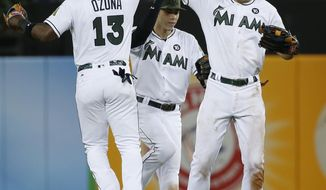 Miami Marlins left fielder Marcell Ozuna (13) center fielder Christian Yelich, center, and right fielder Giancarlo Stanton celebrate after the Marlins defeated the Philadelphia Phillies 4-1 during a baseball game, Monday, May 29, 2017, in Miami. (AP Photo/Wilfredo Lee)