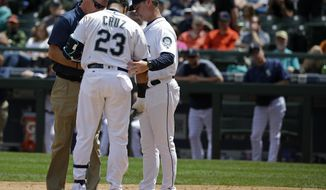 Seattle Mariners manager Scott Servais, right, watches as a trainer talks with Nelson Cruz (23) after Cruz was hit on the top of his left hand with a pitch from Colorado Rockies starting pitcher Kyle Freeland during the third inning of a baseball game, Thursday, June 1, 2017, in Seattle. Cruz remained in the game but was replaced with pinch-hitter Boog Powell in the fifth inning. The Rockies won 6-3. (AP Photo/Ted S. Warren)