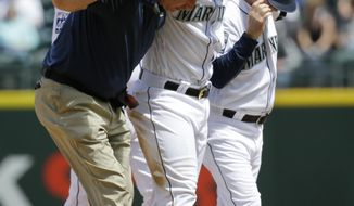 Seattle Mariners' Jean Segura, third from left, is helped off the field by trainer Rob Nodine, left, and first base coach Casey Candaele, right, after suffering an injury sliding into second base in the fourth inning of a baseball game against the Colorado Rockies, Thursday, June 1, 2017, in Seattle. Segura was out on the play and left the game. (AP Photo/Ted S. Warren)
