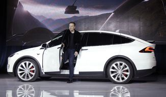 FILE - In this Sept. 29, 2015, file photo, Elon Musk, CEO of Tesla Motors Inc., introduces the Model X car at the company's headquarters in Fremont, Calif. Tesla and General Motors have a budding rivalry that could help determine whether Detroit or Silicon Valley sets the course for the future of the auto industry. Right now Wall Street is favoring the upstart led by flamboyant Elon Musk to the established icon headed by the more restrained Mary Barra. (AP Photo/Marcio Jose Sanchez, File)