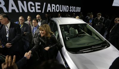 FILE - In this Wednesday, Jan. 6, 2016, file photo, General Motors Co. CEO Mary Barra stands next to the Chevrolet Bolt EV electric car at CES International in Las Vegas. Tesla and General Motors have a budding rivalry that could help determine whether Detroit or Silicon Valley sets the course for the future of the auto industry. Right now Wall Street is favoring the upstart led by flamboyant Elon Musk to the established icon headed by the more restrained Mary Barra. (AP Photo/Gregory Bull, File)