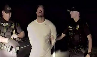 In this image taken from video golfer Tiger Woods stands between two police officers in Jupiter Florida Monday May 29,2017. Police in the US state of Florida have released video of professional golfer Tiger Woods' recent arrest. Jupiter Police released the dash-cam footage of the incident late on Wednesday May 31, 2017. Officers on patrol early on Monday noticed a Mercedes pulled awkwardly to the side of the road with the engine running, the brake lights on and a right indicator blinking. (Jupiter Police Department/via AP)