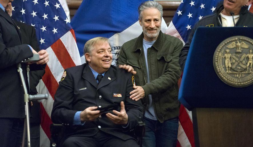 FILE- In this Jan. 9, 2016 file photo, comedian Jon Stewart, right, pats the shoulders of retired FDNY firefighter and Sept. 11 first responder Ray Pfeifer after Pfeifer was given the key to the city at New York's City Hall. Stewart fought back tears Friday, June 2, 2017, during Pfeifer's funeral, as he described his friendship with the retired New York City firefighter who worked in the rescue effort following the Sept. 11 terror attacks. (AP Photo/Craig Ruttle, File)