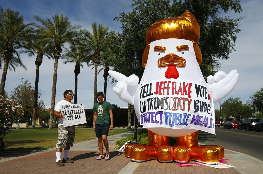 Protesters march in front of a inflatable chicken as they protest in front of an event hosted by the Glendale Chamber of Commerce where Sen. Jeff Flake, R-Ariz., was speaking Tuesday, May 30, 2017, in Glendale, Ariz. (AP Photo/Ross D. Franklin)