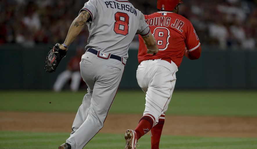 Atlanta Braves second baseman Jace Peterson tags Los Angeles Angels' Eric Young Jr. out in a rundown during the third inning of a baseball game in Anaheim, Calif., Wednesday, May 31, 2017. (AP Photo/Chris Carlson)