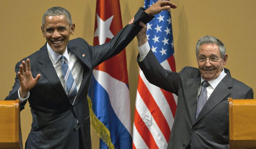 FILE - In this March 21, 2016 file photo, Cuban President Raul Castro, right, lifts up the arm of President Barack Obama at the conclusion of their joint news conference at the Palace of the Revolution, in Havana, Cuba. The current Trump U.S. administration is close to announcing a new policy that would prohibit business with the Cuban military while maintaining the full diplomatic relations restored by Obama, according to a Trump administration official and a person involved in the ongoing policy review. (AP Photo/Ramon Espinosa, File)