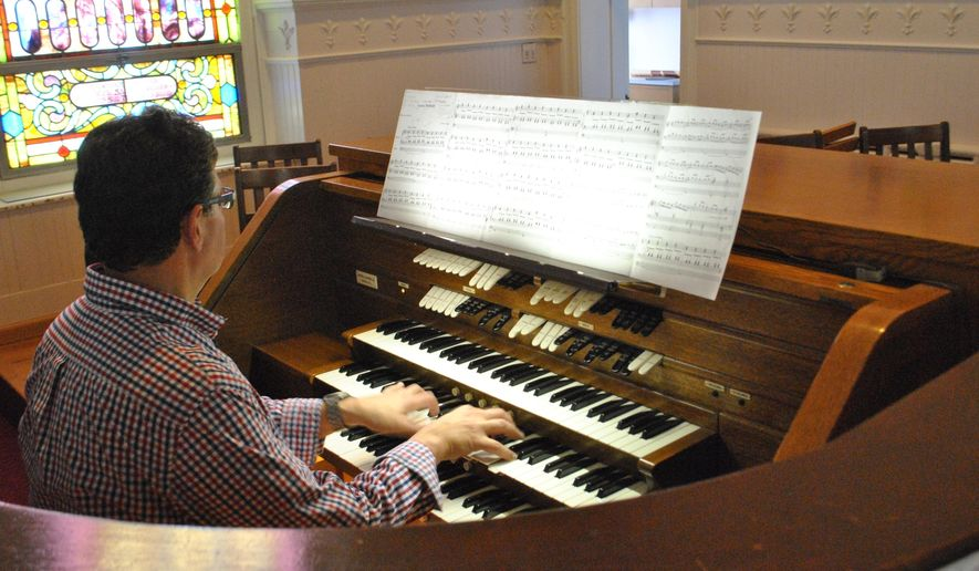 In this recent photo, Mike Capone plays the pipe organ at First Presbyterian Church in Stroudsburg, Pa. The church has a unique project in the works. It will combine two church organs into one over the next two years, thanks to the generous gifting of an Easton, Pa. organ no longer in use.(Howard Frank/Pocono Record via AP)