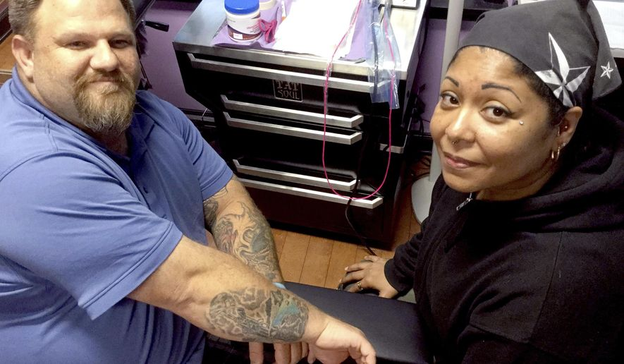 In this Wednesday, May 24, 2017, Dale Wills, left, and wife Clarissa display his battlefield cross tattoo at Beauty Marks, their Port Royal, S.C., tattoo studio. Clarissa Wills created the tattoo and applied it to her husband's arm in memory of friend Sgt. Krisna Nachampassak, who died in Iraq in 2004. (Wade Livingston /The Island Packet via AP)