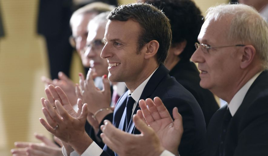 French President Emmanuel Macron, center, and president of the French space agency CNES (Centre national d'etudes spatiales - National Centre for Space Studies) Jean-Yves Le Gall, right, applaud at the CNES headquarters in Paris, France, as they watch a live broadcast of the landing of French astronaut Thomas Pesquet and Russian cosmonaut Oleg Novitskiy in Kazakhstan, ending their marathon 196-day mission to the International Space Station, Friday, June 2, 2017. (Stephane de Sakutin/pool Photo via AP)