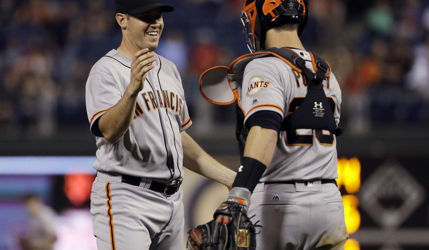 San Francisco Giants starting pitcher Ty Blach, left, and catcher Buster Posey celebrate after a baseball game against the Philadelphia Phillies, Friday, June 2, 2017, in Philadelphia. San Francisco won 10-0. (AP Photo/Matt Slocum)