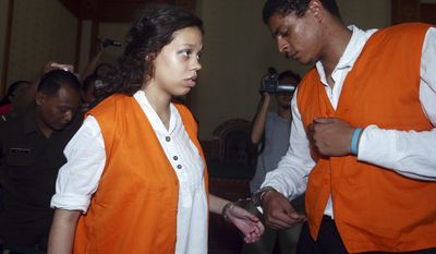 FILE - In this March 31, 2015, file photo, Heather Mack, left, and her boyfriend Tommy Schaefer of Chicago, are handcuffed as they arrive at a courtroom during their trial in Bali, Indonesia. Mack and Schaefer, 19, were both convicted in the killing of Mack's mother, Sheila von Wiese-Mack, whose body was found stuffed inside a suitcase in a taxi at a Bali resort. Bibbs, an Illinois man who typed out emoji and other text messages to advise his cousin thousands of miles away on how to kill a wealthy Chicago woman vacationing in Indonesia was sentenced on Friday, June 2, 2017 to nine years in prison. (AP Photo/Firdia Lisnawati, File)