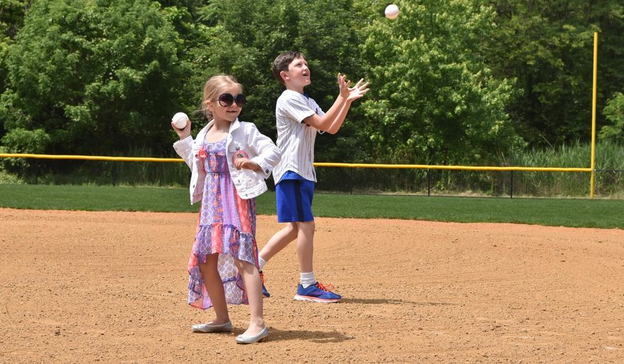 Shannon Dalton Forde' children Kendall and Nicholas, threw the first pitch at the newly named field Shannon Dalton Forde Field, which was built by Major League Baseball and be named Shannon Dalton Forde Field, Friday, June 2, 2017, in Little Ferry, N.J. Shannon, a native of Little Ferry, worked for the New York Mets for 22 years and passed away from breast cancer in 2016. (Marko Georgiev/The Record via AP)