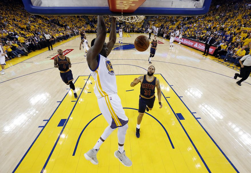 Golden State Warriors' Draymond Green, center, dunks against the Cleveland Cavaliers during the second half in Game 1 of basketball's NBA Finals Thursday, June 1, 2017, in Oakland, Calif. (AP Photo/Marcio Jose Sanchez)