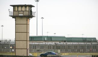 FILE - In this Feb. 1, 2017, file photo,  a prison guard stands at one of the towers at James T. Vaughn Correctional Center during a hostage situation unfolding at the prison in Smyrna. An independent review ordered by Delaware's governor after a deadly inmate riot at the James T. Vaughn Correctional Center, describes the state's maximum-security prison as dangerously overcrowded, critically understaffed, and poorly run and managed. (Suchat Pederson/The Wilmington News-Journal via AP, File)