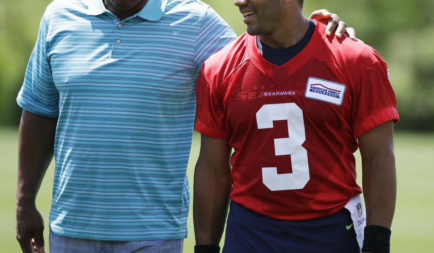 Seattle Seahawks quarterback Russell Wilson, right, walks with former Seahawks quarterback Warren Moon, left, following NFL football practice, Friday, June 2, 2017, in Renton, Wash. (AP Photo/Ted S. Warren)