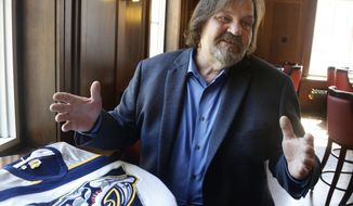 Bob Wolf poses with a Nashville Predators jersey Friday, June 2, 2017, in St. Paul, Minn. The need for secrecy finally is at an end and he's ready to share his tale of the Predators' original catfish caper with the NHL hockey franchise on hockey's biggest stage. Wolf says the idea to toss a catfish grew from a discussion at Wolfy's during the Predators' inaugural season. (AP Photo/Jim Mone)