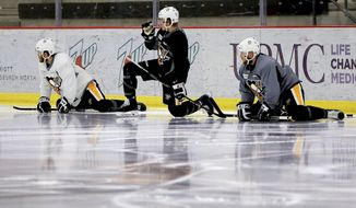 Pittsburgh Penguins' Scott Wilson, left, Jake Guentzel, center, and Chad Ruhwedel, right, are reflected in the ice surface as they stretch during hockey practice at the team training center in Cranberry, Pa., Butler county, on Friday, June 2, 2017. The Penguins are scheduled to play the Nashville Predators in the third game of NHL Stanley Cup Finals in Nashville on Saturday. (AP Photo/Keith Srakocic)