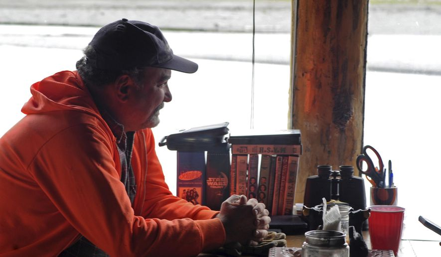ADVANCE FOR WEEKEND JUNE 3-4, 2017 AND THEREAFTER - In this May 27, 2017 photo, Steve Flick, one of the property owners on Dow Island's north bank, relaxes in Natalie and Chad Smyre's cabin on the island in Funny River, Alaska. Flick, a professional construction contractor in Missouri, worked with the Smyres and two other property owners to install an extensive bank restoration project on the island to preempt the Kenai River's erosion that has been washing away feet of their properties each year. (Elizabeth Earl/Peninsula Clarion via AP)