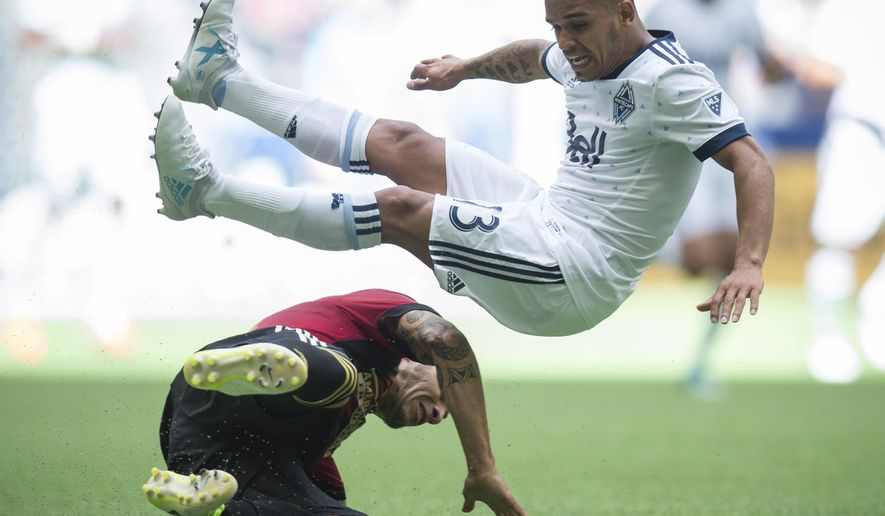 Vancouver Whitecaps' Cristian Techera, right, is upended by Atlanta United's Carlos Carmona during the second half of an MLS soccer match Saturday, June 3, 2017, in Vancouver, British Columbia. (Darryl Dyck/The Canadian Press via AP)