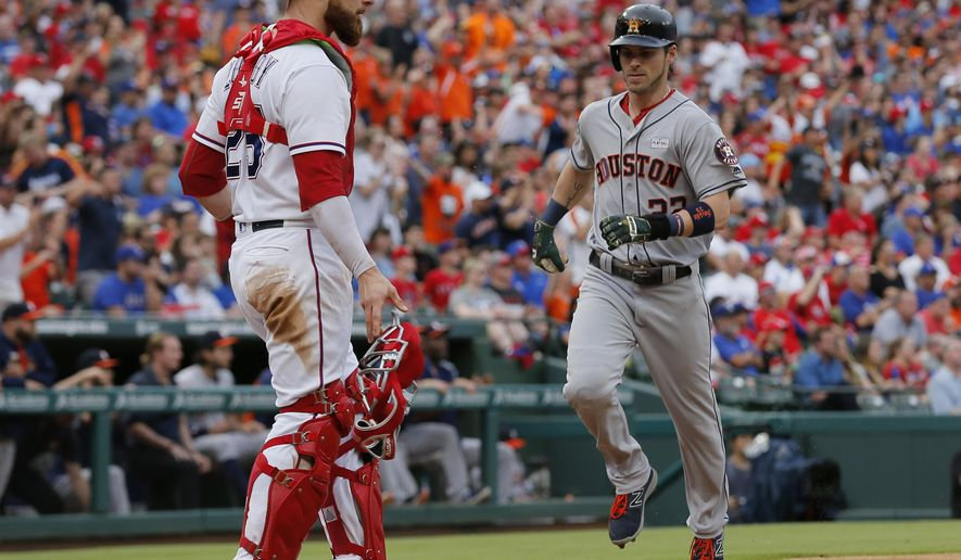 Texas Rangers catcher Jonathan Lucroy, left, stands by the plate as Houston Astros' Josh Reddick (22) scores on a Carlos Beltran single in the third inning of baseball game, Saturday, June 3, 2017, in Arlington, Texas. The hit also scored Jose Altuve. (AP Photo/Tony Gutierrez)