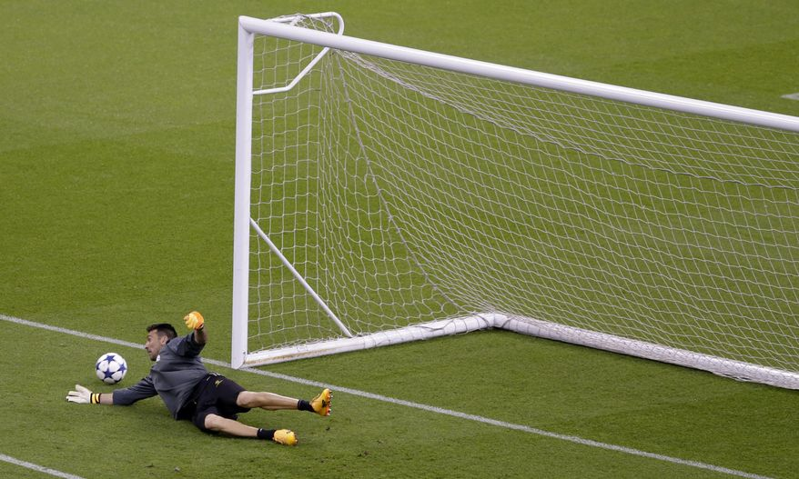 Juventus goalkeeper Gianluigi Buffon dives for a ball during a training session at the Millennium Stadium in Cardiff, Wales, Friday June 2, 2017. Real Madrid will play Juventus in the final of the Champions League soccer match in Cardiff on Saturday. (AP Photo/Alastair Grant)