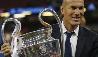 Real Madrid's head coach Zinedine Zidane celebrates with the trophy at the end of the Champions League soccer final between Juventus and Real Madrid at the Millennium Stadium in Cardiff, Wales, Saturday, June 3, 2017. Real won the match 4-1. (AP Photo/Frank Augstein)