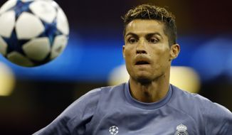 Real Madrid's Cristiano Ronaldo watches the ball during a training session at the Millennium Stadium in Cardiff, Wales Friday June 2, 2017. Real Madrid will play Juventus in the final of the Champions League soccer match in Cardiff on Saturday. (AP Photo/Frank Augstein)