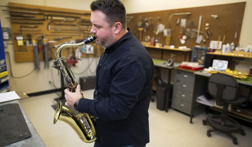 FILE - In this Dec 22, 2016, file photo, Eric Haitz, who is the Omaha Public Schools' band instrument repair technician, tests a saxophone to make sure it is back in working condition after repairing it in Omaha, Neb. (Ryan Soderlin/Omaha World-Herald via AP)