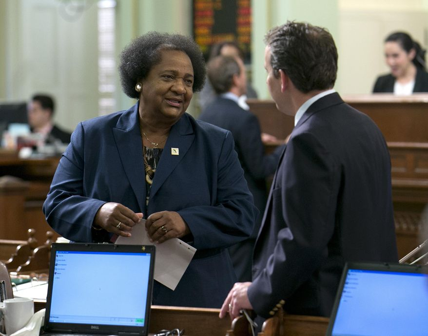 In this Thursday, June 1, 2017 photo, Assemblywoman Shirley Weber, D-San Diego talks with Assembly Marc Levine, D-San Rafael, at the Capitol in Sacramento, Calif. The Assembly approved Weber's bill, AB1220 that would give public school teachers three years to earn a permanent status designation known as tenure. (AP Photo/Rich Pedroncelli)