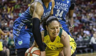 Minnesota's Maya Moore attempts to strip Seattle Storm's Sue Bird of the ball as Bird during the first quarter of a WNBA basketball game Saturday, June 3, 2017, in Seattle. (Dean Rutz/The Seattle Times via AP)