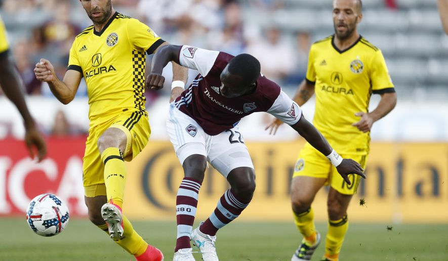 Columbus Crew forward Justin Meram, left, fights for control of the ball with Colorado Rapids midfielder Michael Azira, center, as Crew forward Federico Higuain covers in the first half of an MLS soccer game Saturday, June 3, 2017, in Commerce City, Colo. (AP Photo/David Zalubowski)