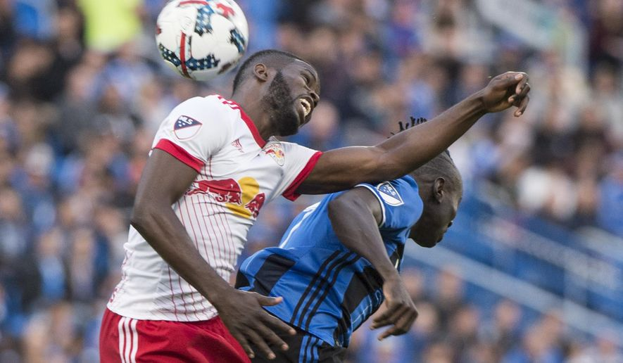 New York Red Bulls defender Kemar Lawrence, left, heads the ball away form Montreal Impact forward Dominic Oduro during the first half of an MLS soccer match Saturday, June 3, 2017, in Montreal. (Paul Chiasson/The Canadian Press via AP)
