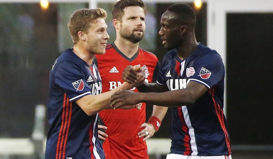 New England Revolution's Benjamin Angoua, right, celebrates his goal with teammate Scott Caldwell, left, in front of Toronto FC's Drew Moor during the first half of an MLS soccer game, Saturday, June 3, 2107, in Foxborough, Mass. (AP Photo/Michael Dwyer)