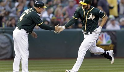 Oakland Athletics' Matt Joyce, right, is congratulated by third base coach Chip Hale (4) after hitting a two-run home run off Washington Nationals' Stephen Strasburg in the third inning of a baseball game Friday, June 2, 2017, in Oakland, Calif. (AP Photo/Ben Margot)