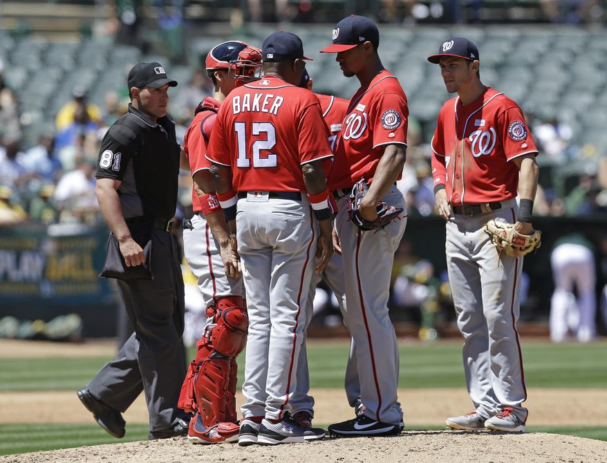 Washington Nationals pitcher Joe Ross, second from right, speaks with manager Dusty Baker (12) in the third inning of a baseball game against the Oakland Athletics, Saturday, June 3, 2017, in Oakland, Calif. (AP Photo/Ben Margot)