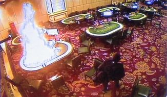 In this image made from security video released by Manila Police and Resorts World Manila on Saturday, June 3, 2017, a gunman walks away after setting fire to a gambling table in the Resorts World Manila entertainment and gambling complex in suburban Pasay city, southeast of Manila, Philippines on Friday, June 2, 2017. Dozens were killed during the attack, mostly from smoke inhalation. (AP Photo/Bullit Marquez)