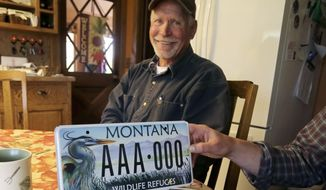 In this May 15, 2017 photo, Dan Severson smiles behind a license plate sponsored by Friends of the Lee Metcalf National Wildlife Refuge at his home in the Burnt Fork area east of Stevensville, Mont.  Years ago, the Friends organization designed a popular state license plate that celebrated National Wildlife Refuges. The license plate generated about $20,000 for the organization. (Perry Backus/Ravalli Republic via AP)