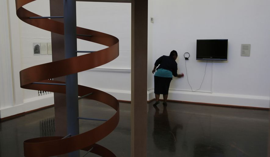 In this photo taken Friday, May 19, 2017, a worker cleans inside the Johannesburg Art Gallery, in Joubert Park, Johannesburg. In the latest chapter of its troubled history, the gallery re-opened on May 7 after a three-month closure that allowed workers to shift art from an area vulnerable to rain leaks because of the theft of roof material into safer storage spaces. (AP Photo/Denis Farrell)