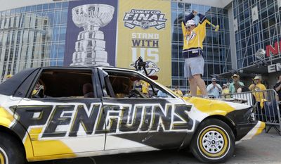 Nashville Predators fan Chas Kelly, of Nashville, Tenn., uses a sledge hammer to hit a car painted in Pittsburgh Penguins colors before Game 3 of the NHL hockey Stanley Cup Finals between the Nashville Predators and the Pittsburgh Penguins Saturday, June 3, 2017, in Nashville, Tenn. (AP Photo/Mark Humphrey)