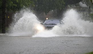 A driver pushes through a flooded neighborhood street caused by a swollen creek during a heavy rain shower, Friday, June 2, 2017, in Richardson, Texas. (AP Photo/Tony Gutierrez)