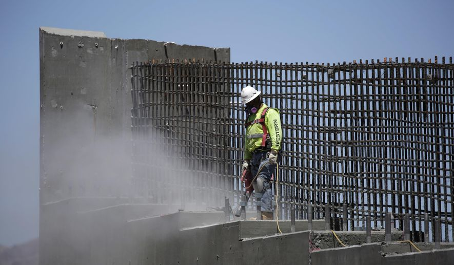 In this May 19, 2017, photo, a man works on the Southern Nevada portion of U.S. Interstate 11 near Boulder City, Nev. President Donald Trump is planning a major push to promote a $1 trillion rebuilding of the nation's roads and bridges as his agenda has struggled in Congress and been overshadowed by White House controversies.  (AP Photo/John Locher)