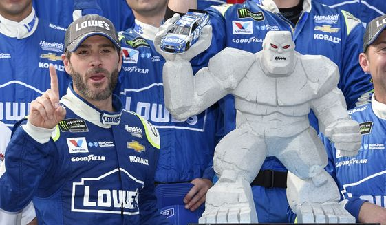 Jimmie Johnson, left, poses with the trophy in Victory Lane after he won a NASCAR Cup series auto race, Sunday, June 4, 2017, at Dover International Speedway in Dover, Del. (AP Photo/Nick Wass)