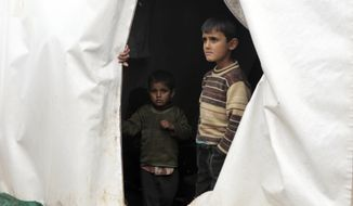 Syrian children, evacuated from Aleppo, stand inside a tent at a refugee camp near Idlib, Syria, Friday, Dec. 16, 2016. Turkey's Foreign Minister Mevlut Cavusoglu says 7,500 civilians have been evacuated from the Syrian city of Aleppo and that he has reached out to Tehran in a bid to keep the process on track.(AP Photo)