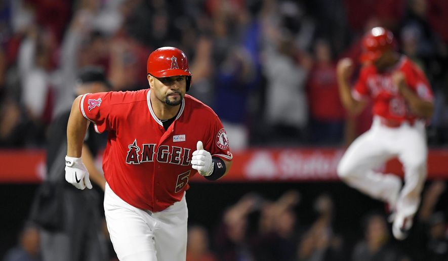 Los Angeles Angels' Albert Pujols, left, runs to first with a grand slam, the 600th homer of his career, while Ben Revere jumps in the background during the fourth inning of the team's baseball game against the Minnesota Twins, Saturday, June 3, 2017, in Anaheim, Calif. (AP Photo/Mark J. Terrill)