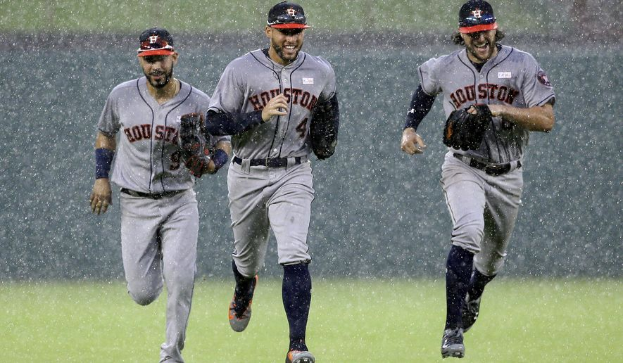 Houston Astros' Marwin Gonzalez, George Springer and Jake Marisnick, right, sprint in from the outfield in a heavy rain after the final out against the Texas Rangers in the ninth inning of a baseball game, Sunday, June 4, 2017, in Arlington, Texas. The Astros won 7-2. (AP Photo/Tony Gutierrez)