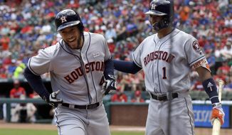 Houston Astros' George Springer (4) and Carlos Correa (1) celebrate Springer's solo home run that came off a pitch from Texas Rangers' Martin Perez in the first inning of a baseball game, Sunday, June 4, 2017, in Arlington, Texas. (AP Photo/Tony Gutierrez)