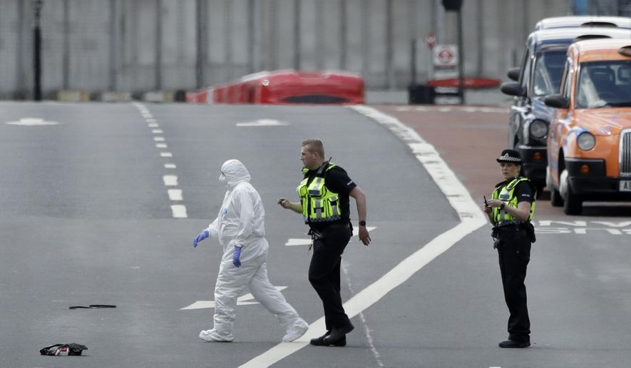 Forensic police work within a cordoned off area after an attack in the London Bridge area of London, Sunday, June 4, 2017. Police specialists collected evidence in the heart of London after a series of attacks described as terrorism killed several people and injured more than 40 others. (AP Photo/Matt Dunham)